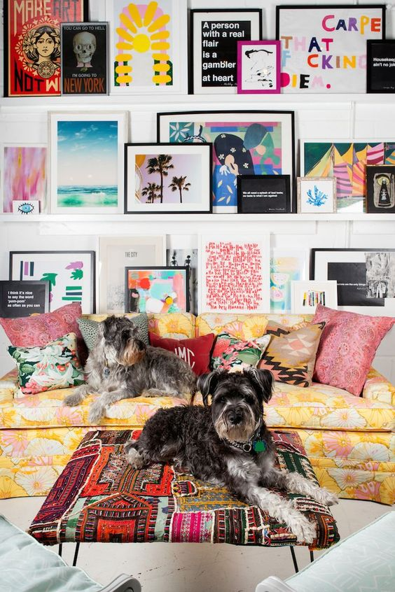 a super bright gallery wall with various kinds of art and posters in mismatching frames placed on white ledges is chic