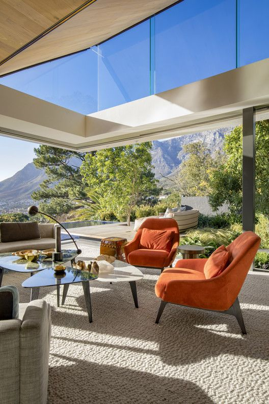a super chic mid-century modern living room with glazed walls and clerestory windows, with cool seating furniture and wonderful views