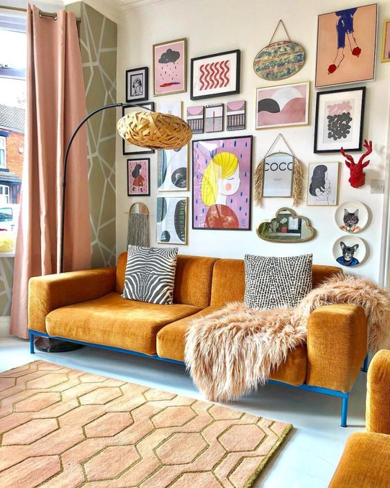a super colorful and chic free form gallery wall with bold artworks and prints of various kinds, a mirror, decorative plates and faux taxidermy
