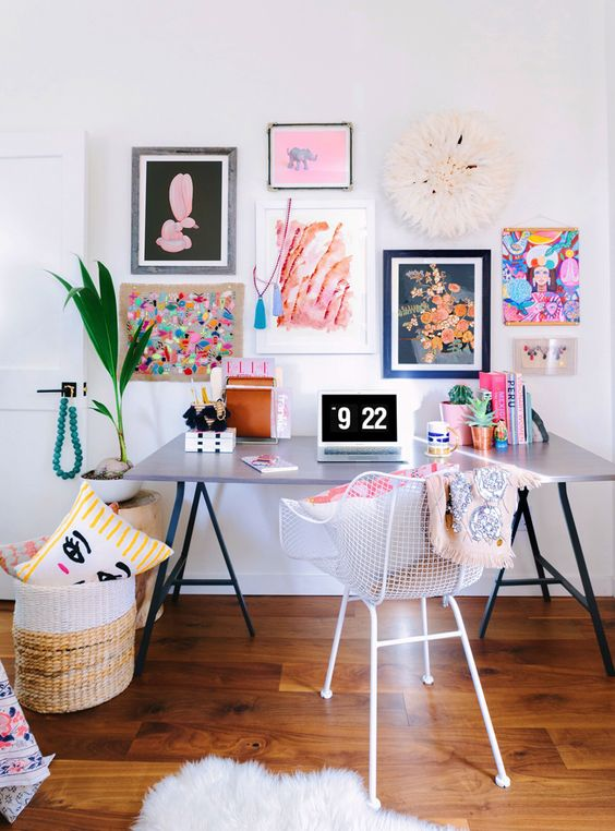 a super colorful gallery wall with mismatching frames and bold floral and abstract art will add a creative touch to the office