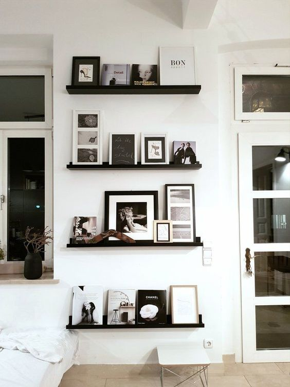 a super elegant gallery wall with black ledges, black and white artworks and books is a chic option for a modern space