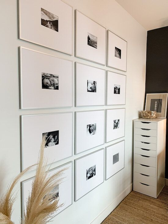 a super modern gallery wall with thin silver frames, mauch matting and small black and white photos