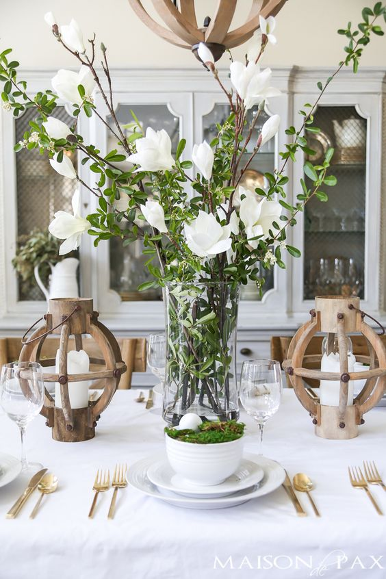 a tall clear vase with greenery and white blooms is a very fresh and beautiful spring centerpiece to rock