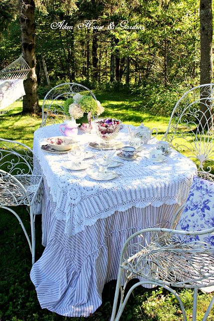 a tea and dining space with a table with lace and matching refined chairs feels exquisite and vintage