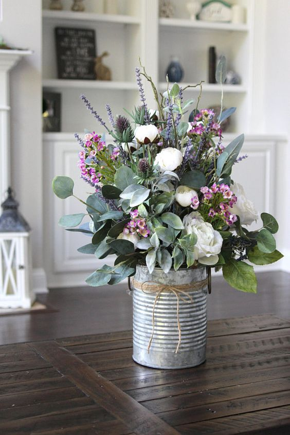 a tin can with white and pink blooms, lavender, thistles and foliage is a pretty rustic decoration for spring