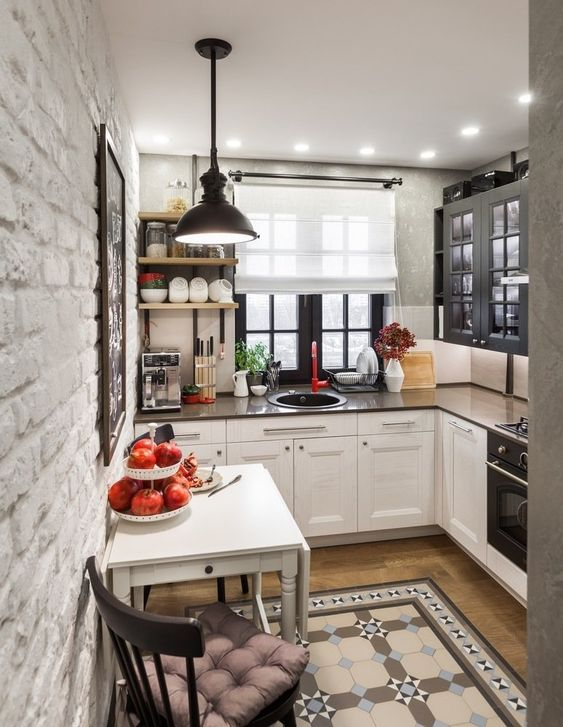 a tiny L-shaped kitchen with two-tone cabinets, dark countertops and a black pendant lamp plus patterned tiles