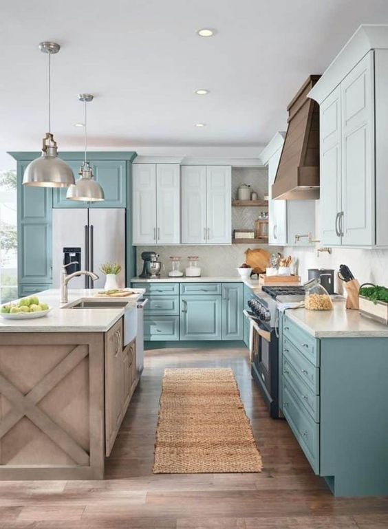 a two tone L shaped kitchen in turquoise and light blue, with a wooden kitchen island and pendant lamps