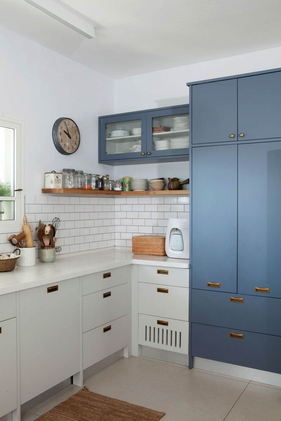 a two tone L shaped kitchen with copper handles and a white subway tile backsplash and a window