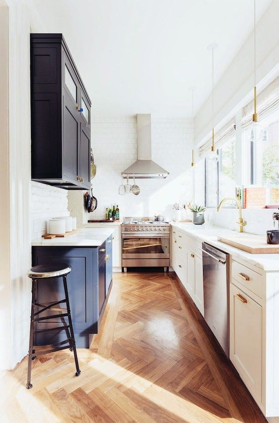 a two-tone kitchen in navy and white with white stone countertops, gold and brass touches and a glazed wall