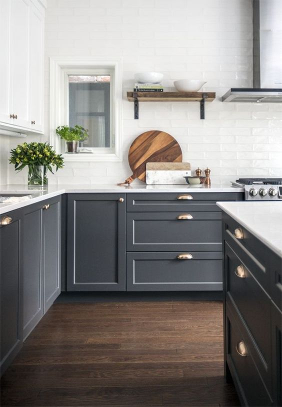 a two tone kitchen with white and grey cabinets, a white tile backsplash and brass touches is very elegant
