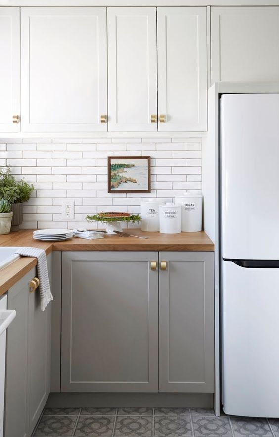 a two-tone kitchen with white and grey cabinets, a white tile backsplash and gold touches is pure chic