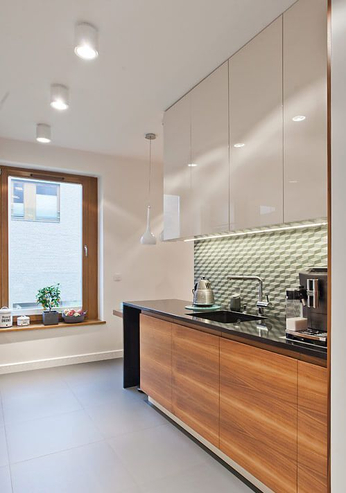 a two tone one wall kitchen with a black stone waterfall countertop, a green tile backsplash and built in lights
