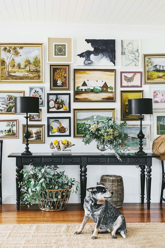 a very chic gallery wall with gilded frames and various types of paintings will blow your mind away