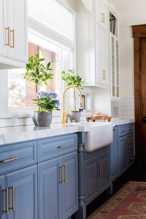 a vintage blue and white one wall kitchen with a white stone countertops and a white tile backsplash plus gold touches