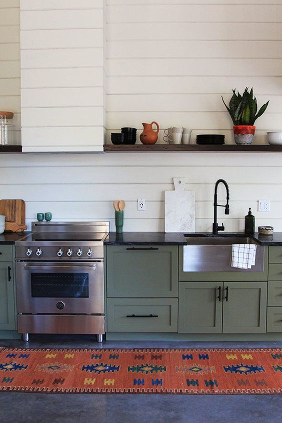 a vintage boho green one wall kitchen with black countertops, a white beadboard backsplash and a hood, a colorful rug