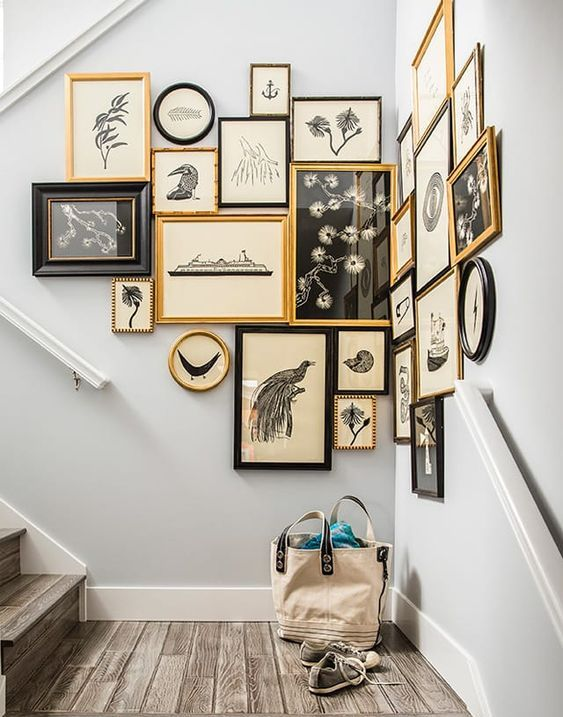 a vintage gallery wall taking the corner, with mismatching black and gold frames and pretty black and white vintage art