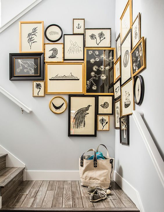 a vintage gallery wall with gold, black frames and vintage blakc and white artworks on vintage paper