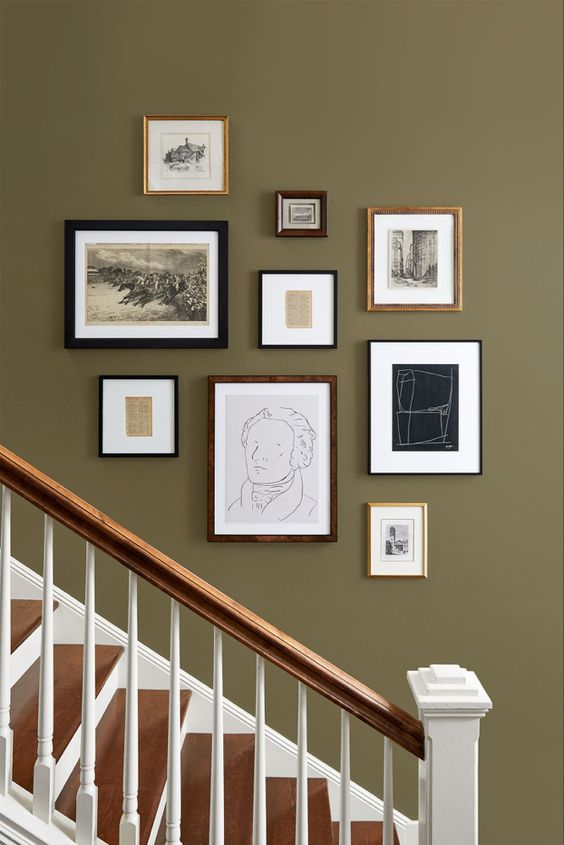 a vintage gallery wall with mismatching frames and artworks, black and white ones for a stylish look