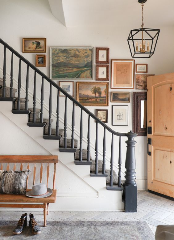 a vintage gallery wall with mismatching frames and landscapes and still-lives is a chic idea to rock