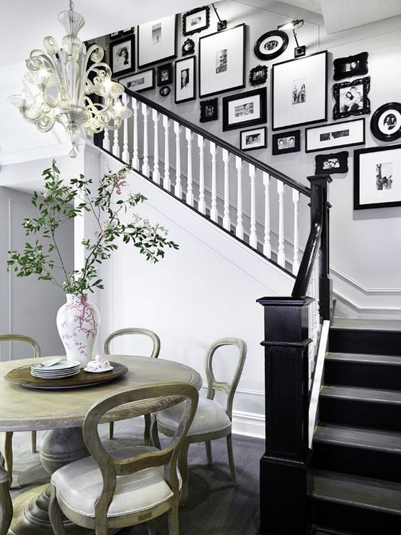 a vintage gallery wall with mismatching refined and modern black frames adds elegant and chic feel to the space