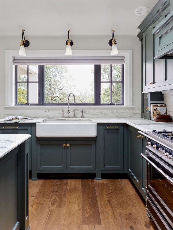 a vintage grey kitchen with shaker style cabinets, white quartz countertops, vintage fixtures and sconces plus mixed metals