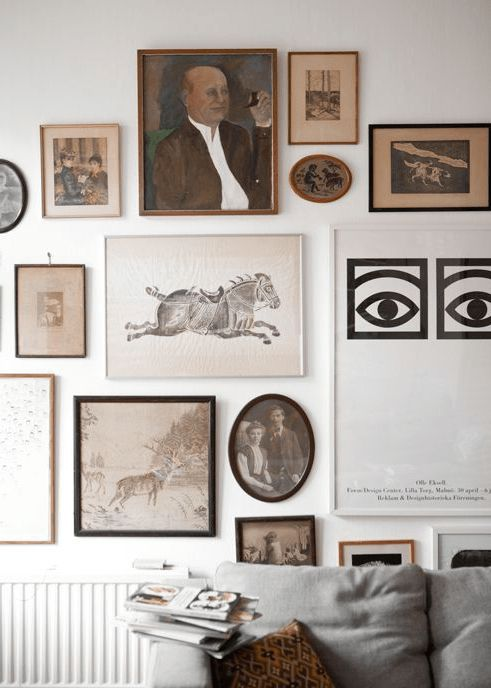 a vintage-inspired free form gallery wall with black, white and gilded frames and various shapes is interesting