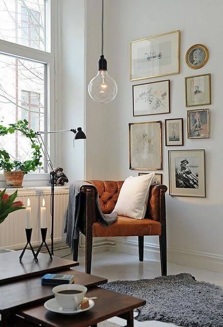 a vintage-inspired free form gallery wall with gold, black and just dark frames and vintage artworks in black and white