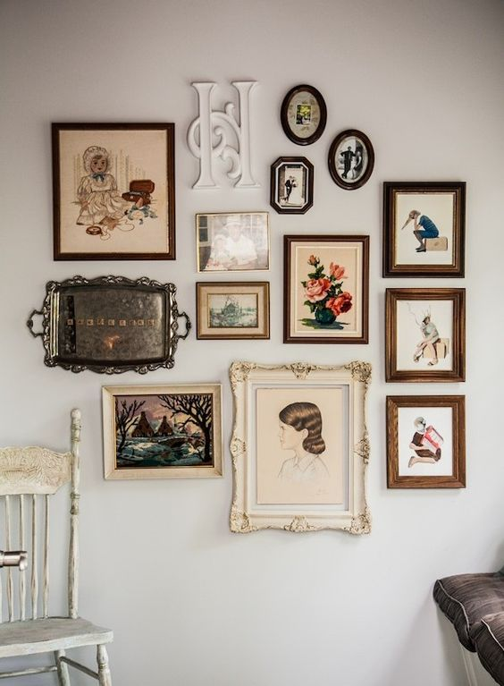 a vintage-inspired gallery wall with elegant frames of various sizes and shapes, with a monogram and even a silver tray