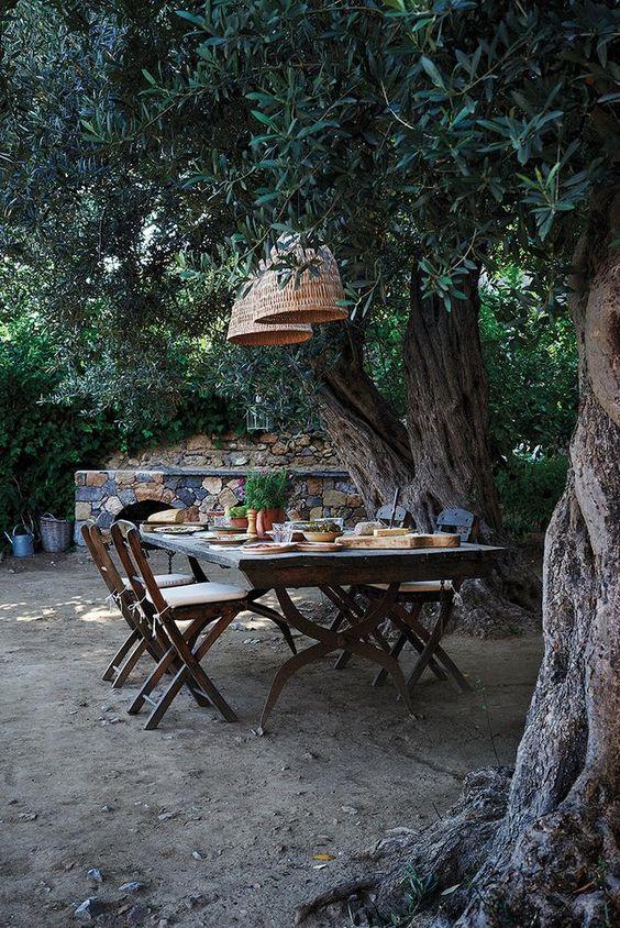 a vintage rustic dining area with a vintage table and folding wooden chairs, rattan lamps is a very cozy space