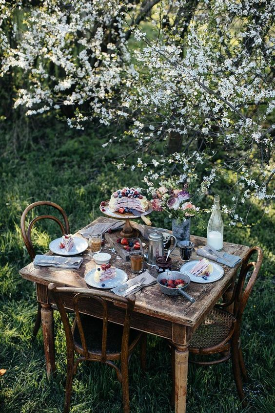 a vintage rustic dining space with shabby chic wooden furniture placed right under the blooming trees