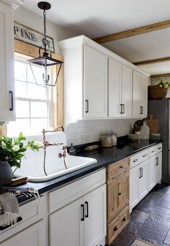 a vintage white one wall kitchen with a black coutnertop, a white subway tile backsplash and black fixtures is pure chic