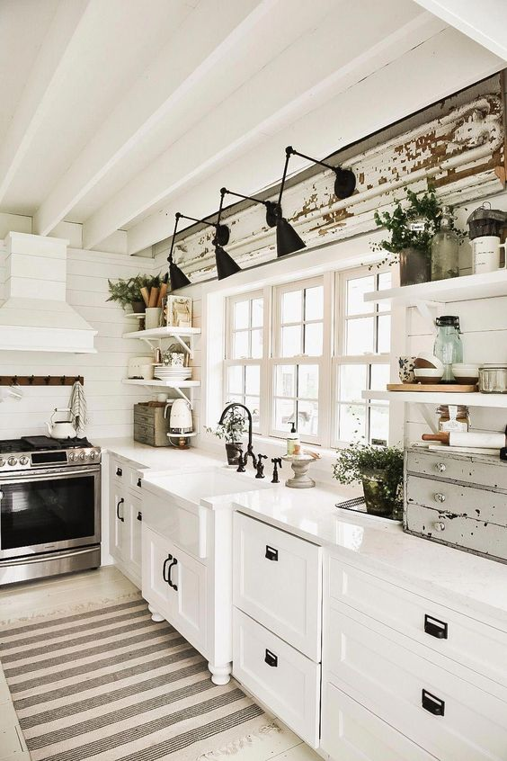 a vintage white one wall ktichen with a shabby chic beam and black sconces plus potted greenery here and there