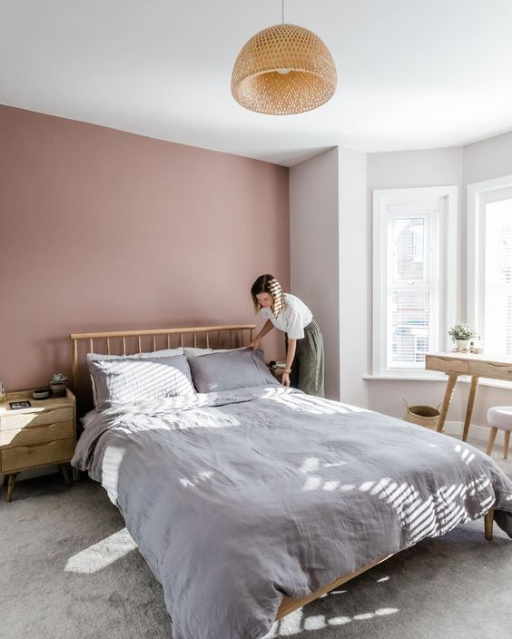 a welcoming and airy bedroom with a mauve accent wall, a wooden bed and wooden furniture, a rattan pendant lamp