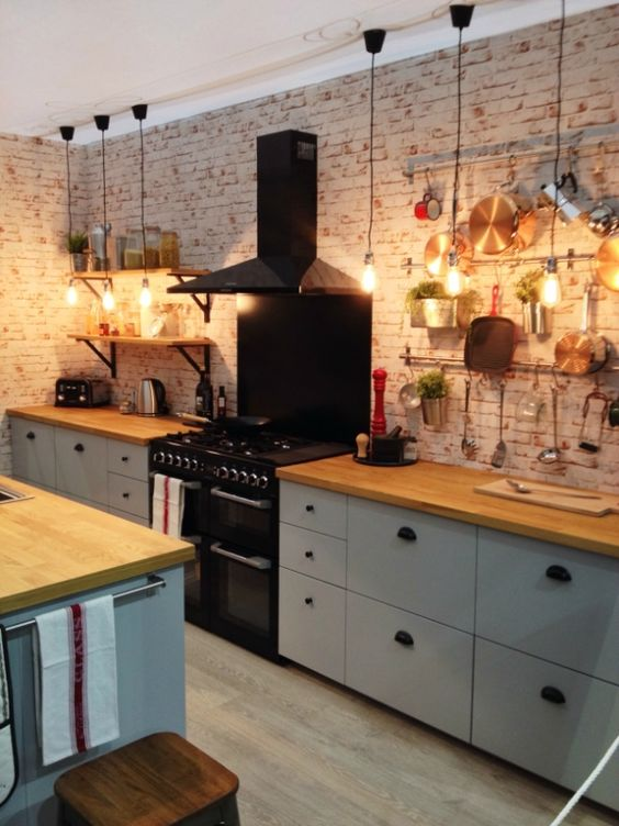 a welcoming contemporary kitchen in neutrals, with butcherblock countertops and a brick wlal plus a kitchen island