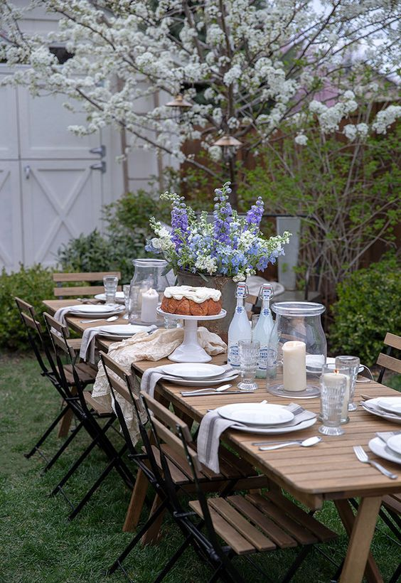 a welcoming dining zone with a wooden table and wooden and metal chairs, neutral linens and blooming trees aroun
