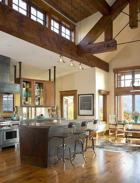 a welcoming rustic space with stained wooden beams, a wooden ceiling and pendant lamps, large usual windows and additional clerestory ones