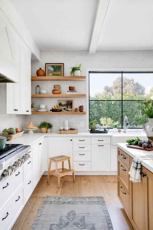 a welcoming white L-shaped kitchen in farmhouse style with light-stained wooden items and a large window