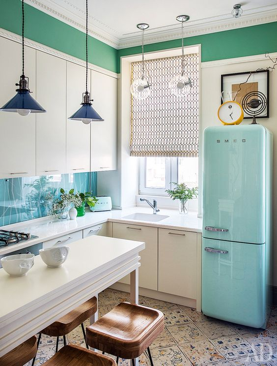 a white L shaped kitchen with a blue fridge, pendant lamps and patterned tiles on the floor is a pretty and catchy space