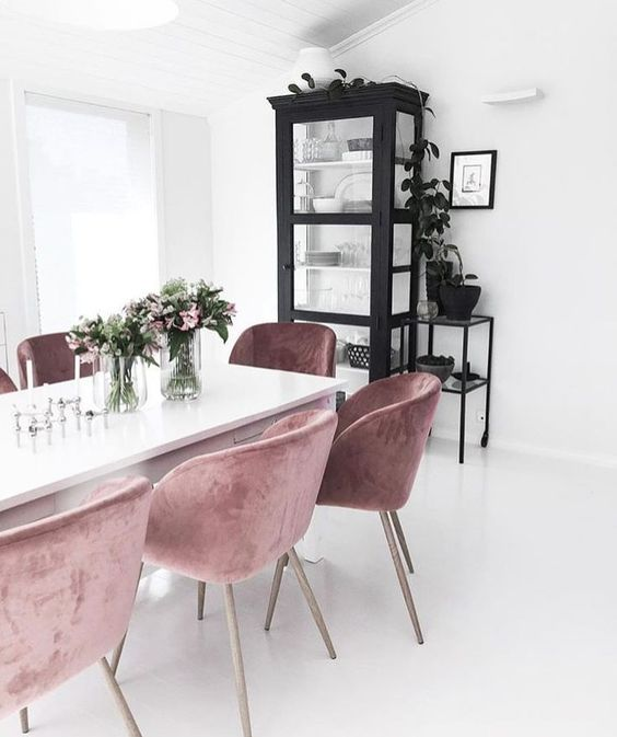 a white Nordic dining room with a black buffet and mauve chairs, some plants and blooms