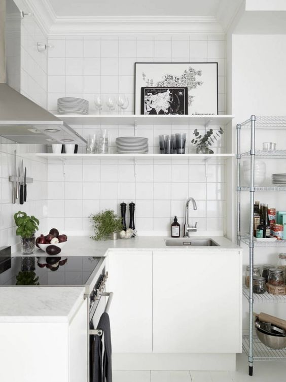 a white Nordic kitchen with a white tile backsplash, stainless steel appliances is a very airy space