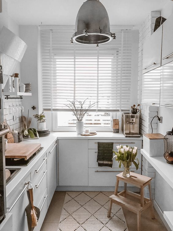 a white Scandinavian L shaped kitchen with a white tile backsplash and countertops, wooden surfaces is super cool