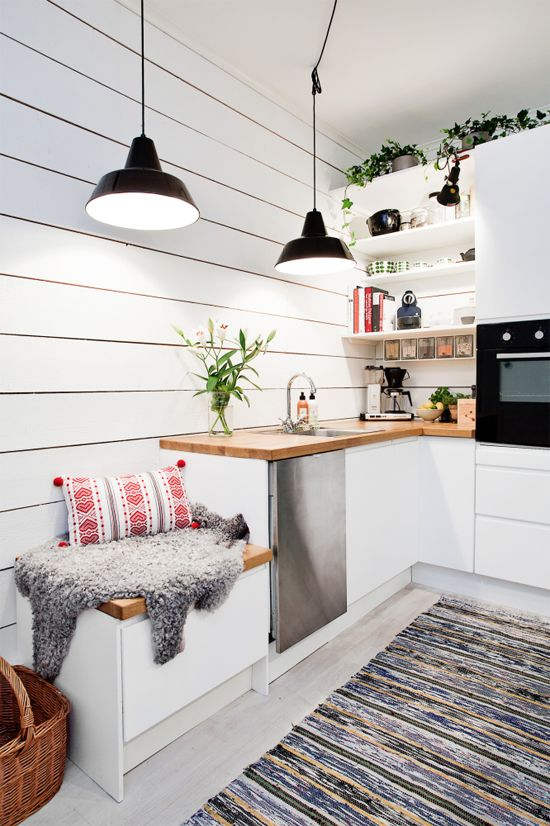 a white Scandinavian kitchen with butcherblock countertops, black pendant lamps and potted greenery