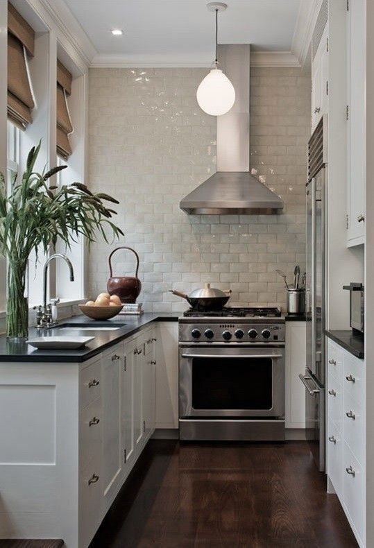 a white U-shaped kitchen with black countertops, a neutral tile backsplash and some greenery is a cozy little space