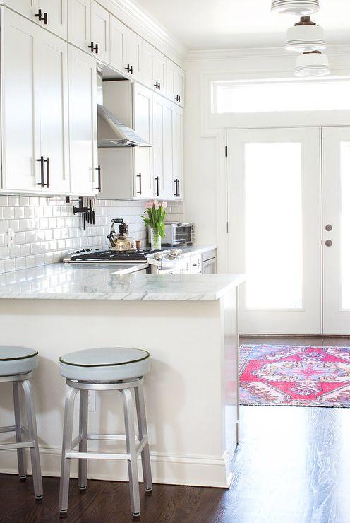 a white farmhouse L-shaped kitchen with white stone countertops and a white subway tile backsplash plus dark handles