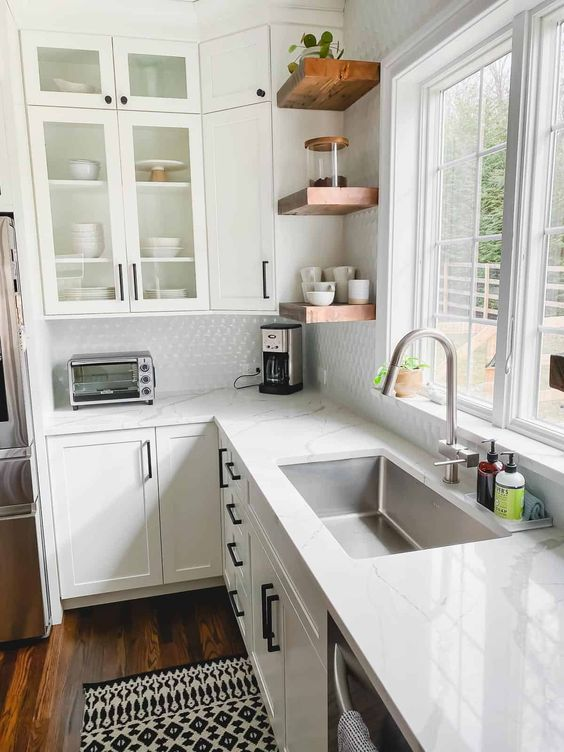 a white farmhouse L-shaped kitchen with white stone countertops, rich-stained wooden shelves