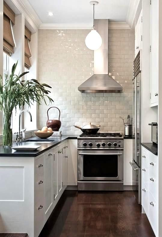 a white farmhouse U-shaped kitchen with a black countertop, a glazed tile backsplash and stainless steel appliances
