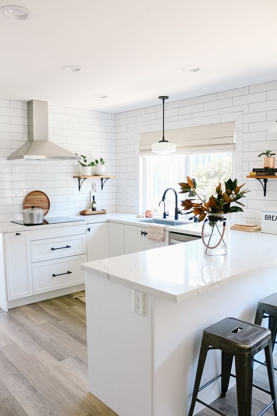 a white farmhouse U-shaped kitchen with a white subway tile backsplash and white stone countertops