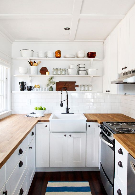 a white farmhouse U-shaped kitchen with butcherblock countertops, black fixtures and open shelves