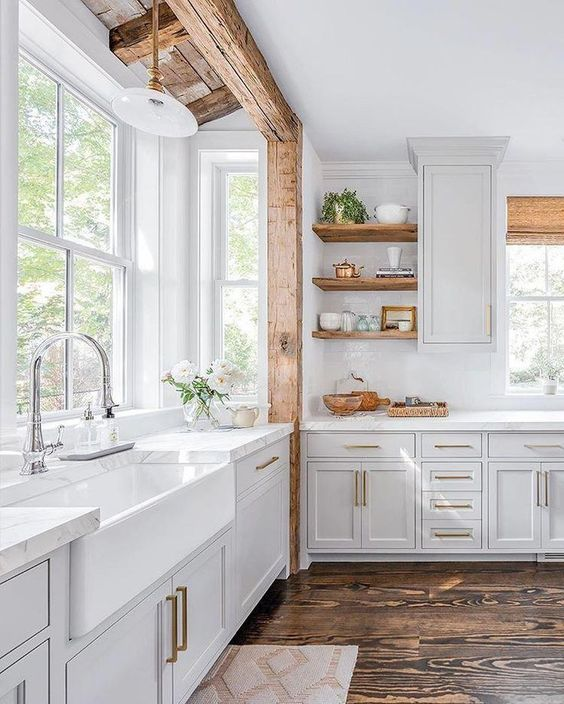 a white farmhouse kitchen with a wooden beam, wooden shelves and woven shades plus brass touches