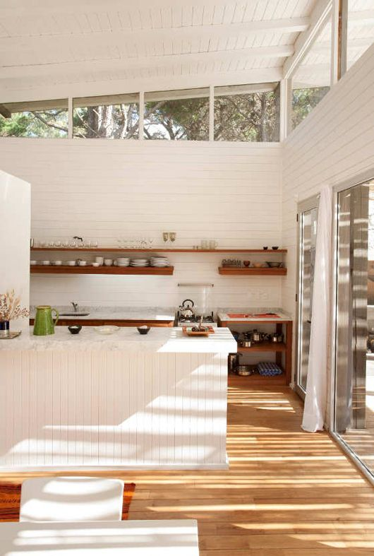 a white farmhouse kitchen with beadboard cladding the walls and clerestory windows that bring light inside and sliding doors